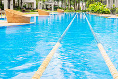 Swimming path in nice blue swimming pool and round resting chair Royalty Free Stock Photos