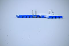 Snow-covered swimming platform in frozen lake Royalty Free Stock Photography