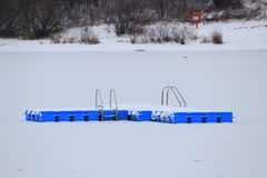 Swimming platform in snowy lake scenery Royalty Free Stock Images