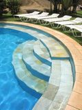 Swimming pool - 1. Inviting lounge chairs on grass around a crescent-shaped swimming pool stock images