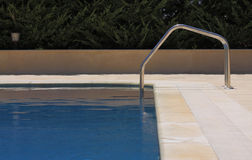 Swimming Pool. Blue-tiled swimming pool with step ladder Stock Images