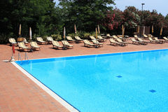 Swimming pool. With sun-beds and umbrellas Stock Photography