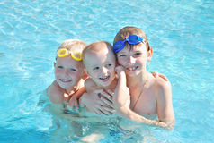 Swimming pool. Three brothers playing in the swimming pool Royalty Free Stock Photography