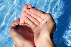 Swimming pool. Water falling from the hands on a swimming pool Royalty Free Stock Image