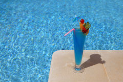 Swimming-pool. A decorated cocktail (blue Lagoon) on the swimming pool border - Lifestyle concept Stock Image