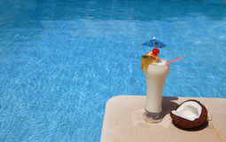 Swimming-pool. A decorated cocktail (Pina Colada) on the swimming pool border - Lifestyle concept Stock Images