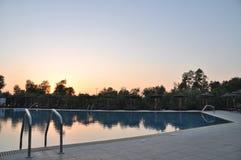Swimming pool. Gorgeous resort swimming pool with umbrellas during sunset Stock Photos