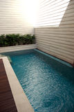 Swimming Pool. A Swimming Pool with blue water and and white wall and wood background Royalty Free Stock Photography