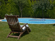Swimming pool. Backyard swimming pool view with an armchair Stock Photos