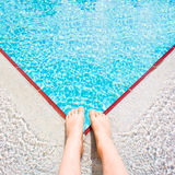 Swimming pool. A child's feet at the edge of a bright blue swimming pool Stock Photos