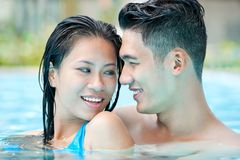 In swimming pool. Happy couple swimming in pool Stock Images