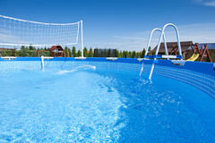 Swimming pool. Details of the beautiful, unoccupied outdoor swimming pool with volleyball equipment Stock Photography
