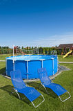 Swimming pool. Two blue deckchair on the lawn in front of the outdoor swimming pool Stock Images