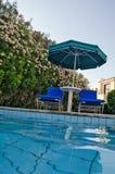 Swimming pool. Chairs and umbrella near swimming pool Stock Image