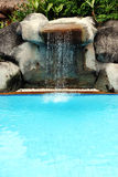 Swimming pool. Man-made waterfall flowing into a swimming pool at a tropical spa resort in Phuket, Thailand - travel and tourism Stock Images