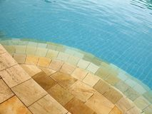 Swimming pool - 5. Yellow stone steps leading into a blue swimming pool. Surface waves distort the view, giving it an abstract feel royalty free stock photography