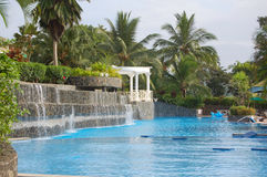 Swimming pool. Luxury swimming pool with waterfalls and palms in the background stock image