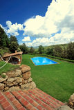 Swimming Pool. Luxury in-ground swimming pool with an open pool house nearby, in the middle of a yard overlooking a remote area of trees and ground.  Brick steps Stock Photos