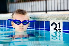 Swimming in the pool. Young boy wearing diving mask or goggles in the swimming pool afternoon Royalty Free Stock Photos