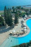Swimming pool. Hotel territory: swimming pool, sunbeds, trees and sea Stock Photo