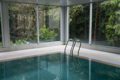Swimming pool. Indoor swimming pool surrounded by leafy trees in an idyllic landscape royalty free stock photo