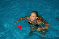 Swimming pool at afternoon. Young pretty woman and one flower Stock Image