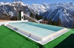 Swimming pool against snowy Alps Stock Images