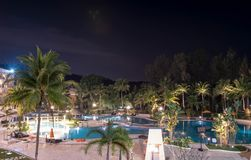 Swimming pool area in a beach hotel resort during night with trees and smooth blue swimming pool water reflecting lights long stock photography