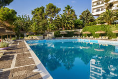 Swimming pool area of hotel, Greece. Swimming pool area of hotel with sun umbrella and beach chair, Greece royalty free stock image