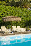 Swimming pool area of hotel. With sun umbrella and beach chair stock image