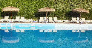 Swimming pool area of hotel. With sun umbrella and beach chair royalty free stock photo