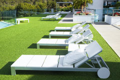 Swimming pool area with  white sun beds at the modern resort. Stock Photos