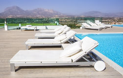 Swimming pool area with  white sun beds at the modern resort. Royalty Free Stock Images