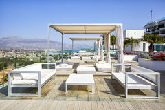 Swimming pool area with  white sun beds at the modern resort. Stock Photography