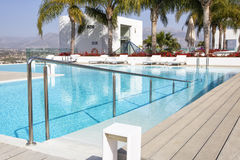 Swimming pool area with  white sun beds at the modern resort. Royalty Free Stock Photos