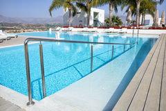 Swimming pool area with  white sun beds at the modern resort. Stock Images