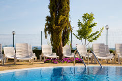 Swimming pool with arranged white sunbeds Stock Photography