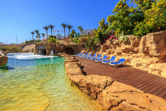 Swimming pool with artificial waterfall and sun loungers. Luxury buildings, palm trees, behind it on a beautiful resort in Egypt stock image