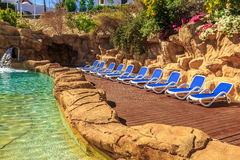 Swimming pool with artificial waterfall and sun loungers Stock Photo