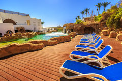 Swimming pool with artificial waterfall and sun loungers. Luxury buildings, palm trees, behind it on a beautiful resort in Egypt royalty free stock image
