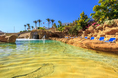 Swimming pool with artificial waterfall and sun loungers Royalty Free Stock Image