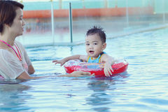 Swimming pool. Asian family in swim ring playing on swimming pool Stock Photos