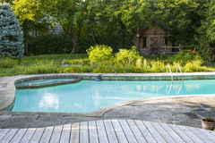 Swimming pool in backyard. Backyard with outdoor inground residential swimming pool, garden, deck and stone patio Royalty Free Stock Photo