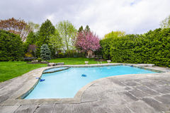 Swimming pool in backyard. Backyard with outdoor inground residential private swimming pool and stone patio Stock Photos