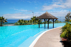 Swimming pool with Bali type hut and beach. Of luxury hotel, Tenerife island, Spain stock images