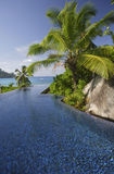 Swimming pool of the Banyan Tree Hotel with ocean in background, Anse Intendance, Mahe`, Seychelles Royalty Free Stock Photo