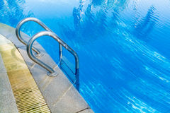 Swimming pool bar ladder in light blue water. Swimming pool bar, stainless ladder in light blue water Stock Image