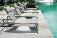 Swimming pool with beach chairs. On pool deck Stock Image