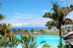 Swimming pool and beach at luxury hotel Stock Photo