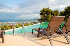Swimming pool by a beach at the modern luxury hotel. Halkidiki, Greece Stock Photos